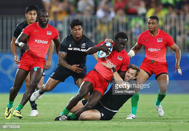 Billy Odhiambo of Kenya is tackled by Tim Mikkelson and Regan Ware of New Zealand during the Men's Rugby Sevens Pool C match between New Zealand and...