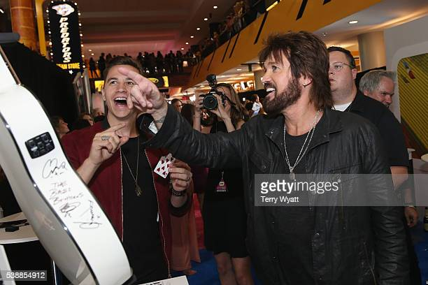 Billy Ray Cyrus with magician Justin Flom arrives at the 2016 CMT Music Awards at Bridgestone Arena on June 8 2016 in Nashville Tennessee