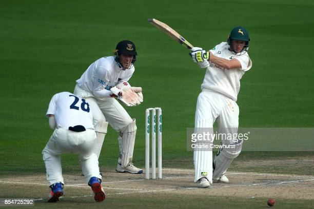 Billy Root of Nottinghamshire hits out while Sussex keeper Michael Burgess looks on during day three of the Specsavers County Championship Division...