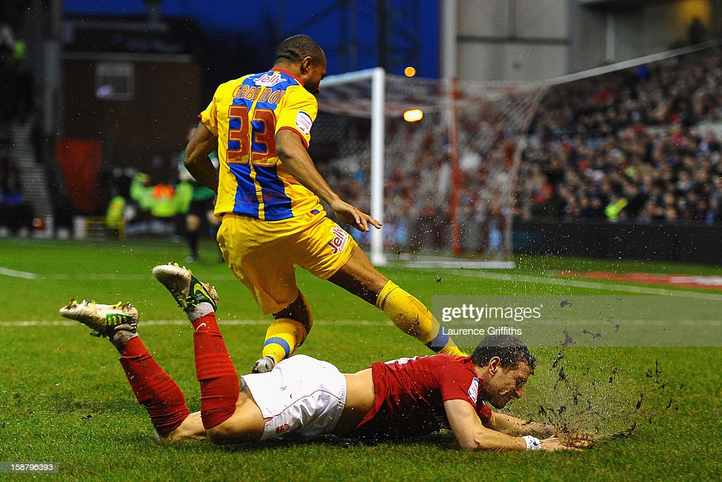 Billy Sharp of Nottingham Forest slides through the mud as he challenges Danny Gabbidon of Crystal Palace during the npower Championship match between Nottingham Forest and Crystal Palace at City Ground on December 29, 2012 in Nottingham, England.