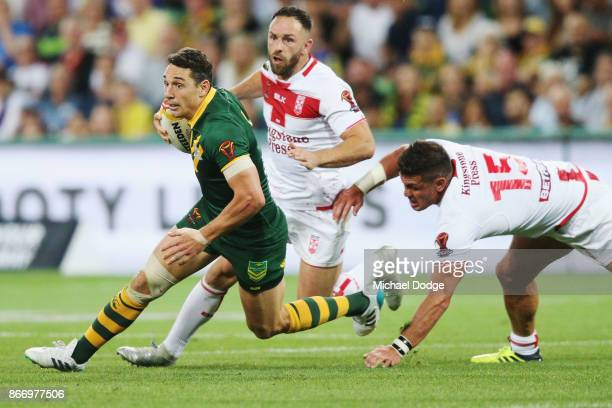 Billy Slater of the Kangaroos runs with the ball past Chris Heighington of England during the 2017 Rugby League World Cup match between the...