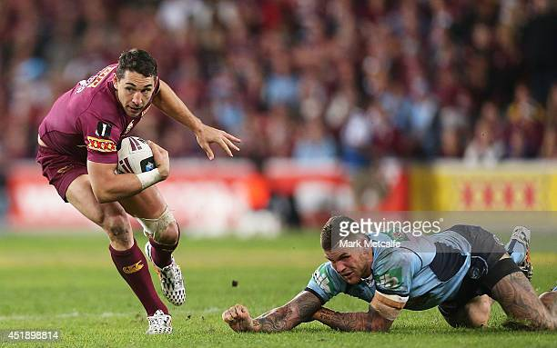 Billy Slater of the Maroons evades the tackle of Josh Dugan of the Blues during game three of the State of Origin series between the Queensland...