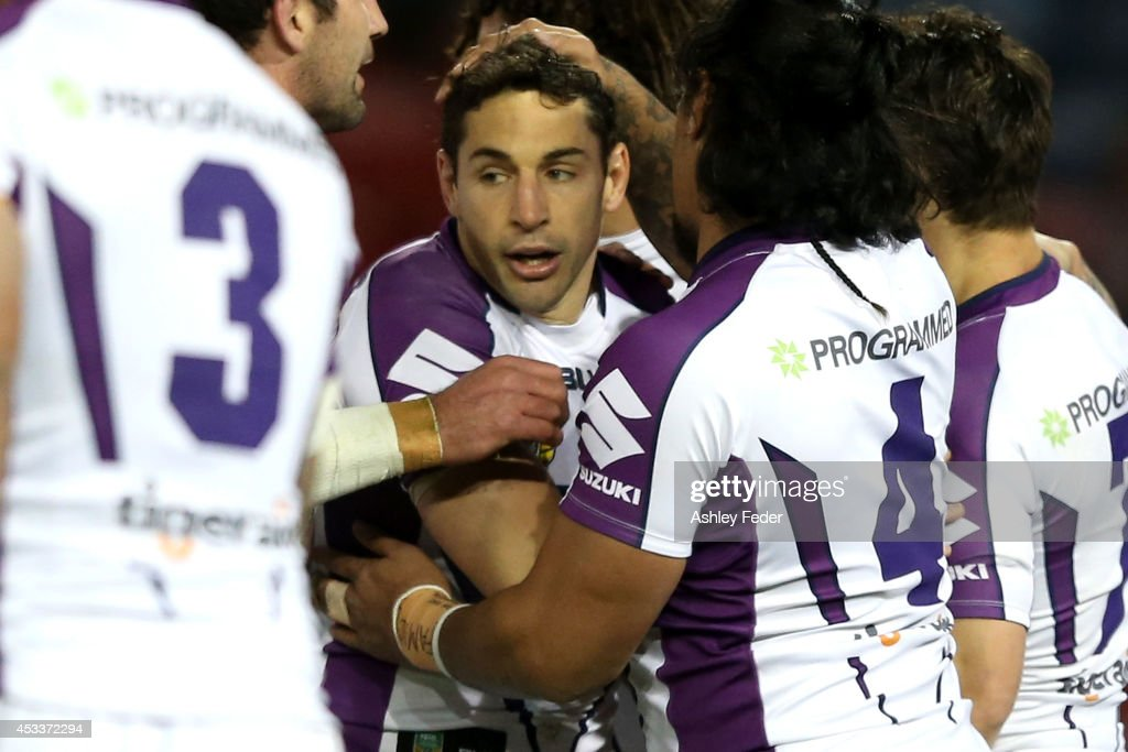 Billy Slater of the Storm celebrates a try with teammates during the round 22 NRL match between the Newcastle Knights and the Melbourne Storm at...