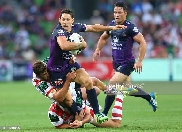 Billy Slater of the Storm is tackled by Gareth Widdop and Will Matthews of the Dragons during the round one NRL match between the Melbourne Storm and...