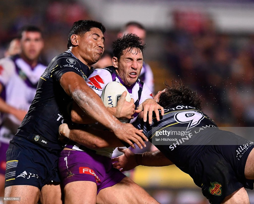 Billy Slater of the Storm is tackled by Jason Taumalolo and Jake Granville of the Cowboys during the round 22 NRL match between the North Queensland Cowboys and the Melbourne Storm at 1300SMILES Stadium on August 4, 2017 in Townsville, Australia.