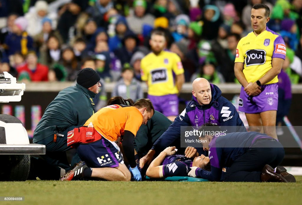 Billy Slater of the Storm receives attention after a tackle by Iosia Soliola of the Raiders during the round 20 NRL match between the Canberra Raiders and the Melbourne Storm at GIO Stadium on July 22, 2017 in Canberra, Australia.