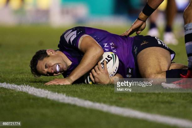 Billy Slater of the Storm shows discomfort and appears to be injured in a tackle during the round 14 NRL match between the Cronulla Sharks and the...