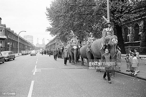 Billy Smart's Circus Elephants with riders and mahouts and trainers march along Queenstown Road in South London with Battersea Power Station in the...