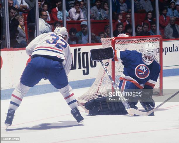 Billy Smith of the New York Islanders slides to save a shot taken by Claude Lemieux of the Montreal Canadiens at the side of the net Circa 1983 at...