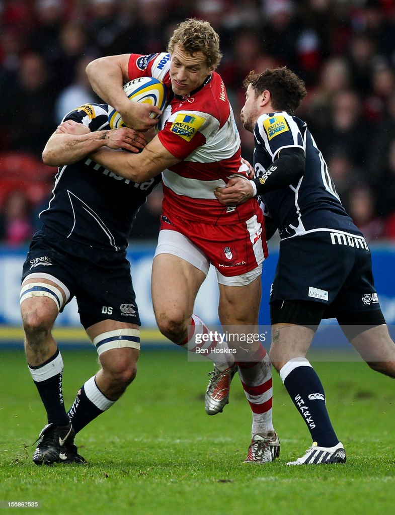 Billy Twelvetrees of Gloucester is tackled by David Seymour (L) and Danny Cipriani (R) of Sale during the Aviva Premiership match between Gloucester and Sale Sharks at the Kingsholm Stadium on November 24, 2012 in Gloucester, England.