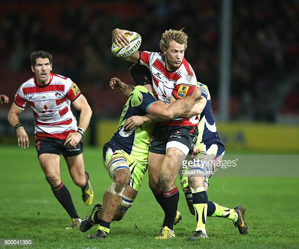 Billy Twelvetrees of Gloucester is tackled by Josh Beaumont and Neil Briggs during the Aviva Premiership match between Gloucester and Sale Sharks at...