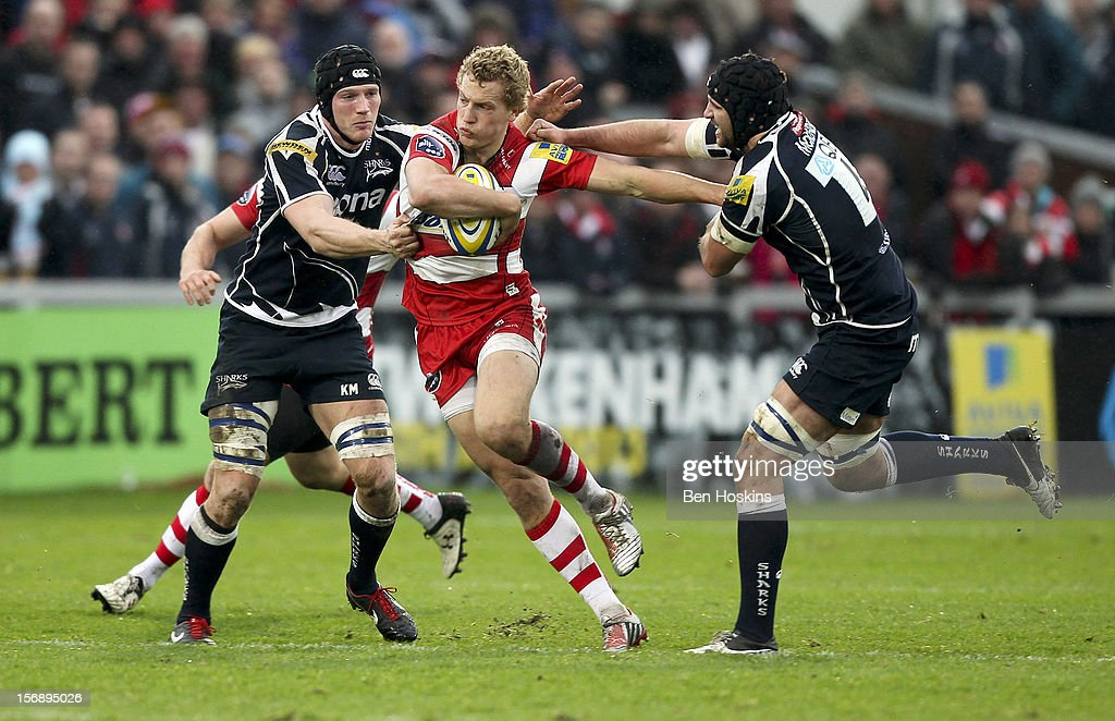 Billy Twelvetrees of Gloucester is tackled by Kearnan Myall (L) and Fraser McKenzie (R) of Sale during the Aviva Premiership match between Gloucester and Sale Sharks at the Kingsholm Stadium on November 24, 2012 in Gloucester, England.