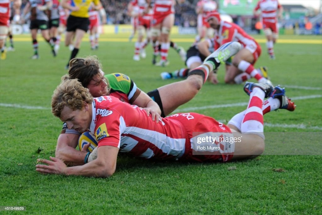 Billy Twelvetrees of Gloucester Rugby dives over to score a try despite the efforts of Luke Wallace of Harlequins during the Aviva Premiership Rugby match between Harlequins and Gloucester at Twickenham Stoop on November 23, 2013 in London, England.