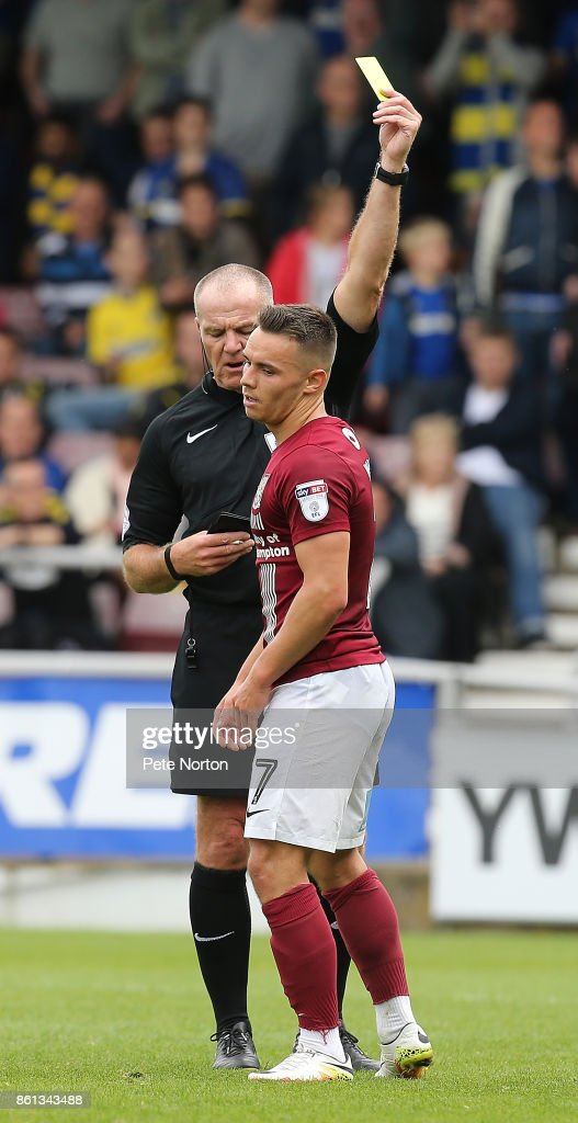 Billy Waters of Northampton Town is shown a yellow card by referee Graham Salisbury during the Sky Bet League One match between Northampton Town and A.F.C. Wimbledon at Sixfields on October 14, 2017 in Northampton, England.