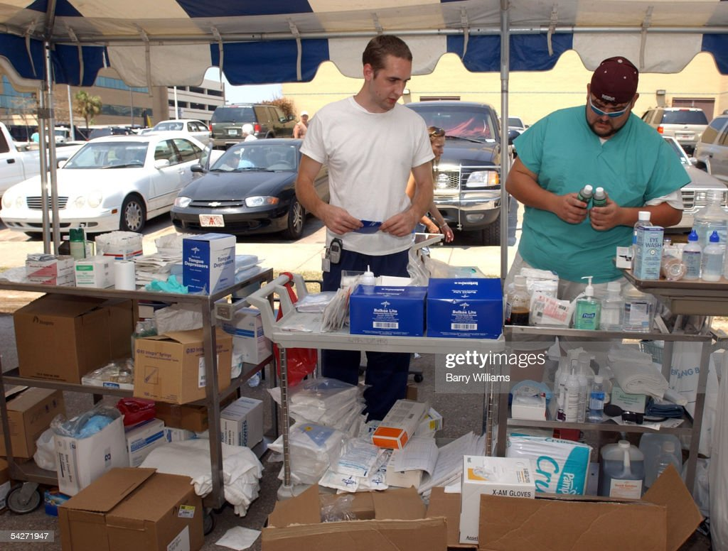 Biloxi Regional Medical Center employees Brian Cunningham (C) and Michael Pernell (R) stock supplies in an outdoor clinic September 2, 2005 in Biloxi, Mississippi. The hospital and FEMA have set up medical facilities in the hospital's parking lot to treat storm related illnesses and injuries. The hospital has already reported one death from Vibro Vulnificus, a bacterial disease spread by contaminated water from Hurricane Katrina infecting wounds.