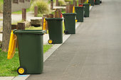 Row of wheelie bins emptied on bin day in suburban western Sydney. Yellow for recyclable material, red for general waste.