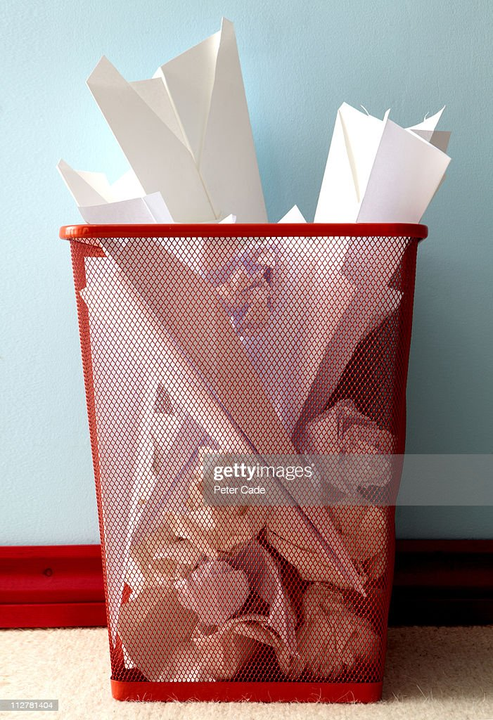 Bin full of screwed up paper and paper aeroplanes : Stock Photo
