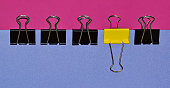 A row of black binder clips with a single yellow one for contrast. Set against a split-tone background of bold pink and purple paper.