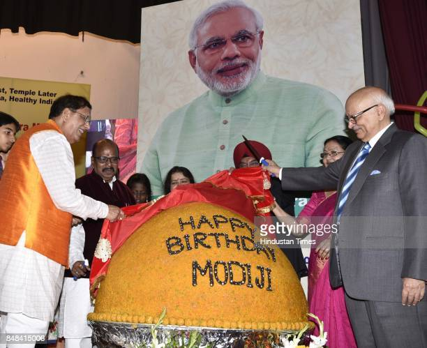 Bindeshwar Pathak Founder Sulabh International and BP Singh with school children cutting a 567 Kg laddoo to celebrate the birthday of Prime Minister...