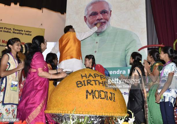 Bindeshwar Pathak Founder Sulabh International with school children cutting a 567 Kg laddoo to celebrate the birthday of Prime Minister Narendra Modi...