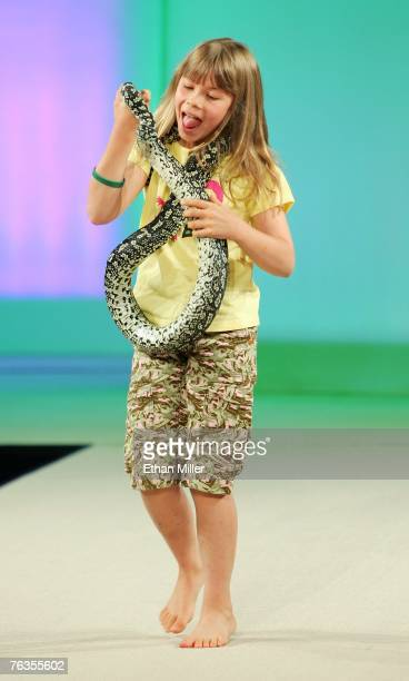 Bindi Irwin carries a snake as she walks the catwalk during the global launch of her Bindi Wear International fashion line at the MAGIC convention at...