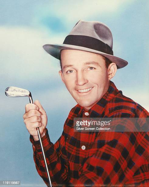 Bing Crosby US actor and singer wearing a grey fedora with a black band and a redandblack check shirt and holding a golf club engraved 'Bing Crosby'...