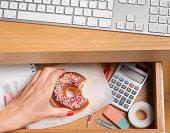 Binge eater hiding doughnut in desk drawer