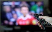 Hand with remote control and blurred TV in the background