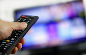 Hand holding remote control with blurred TV set in the background