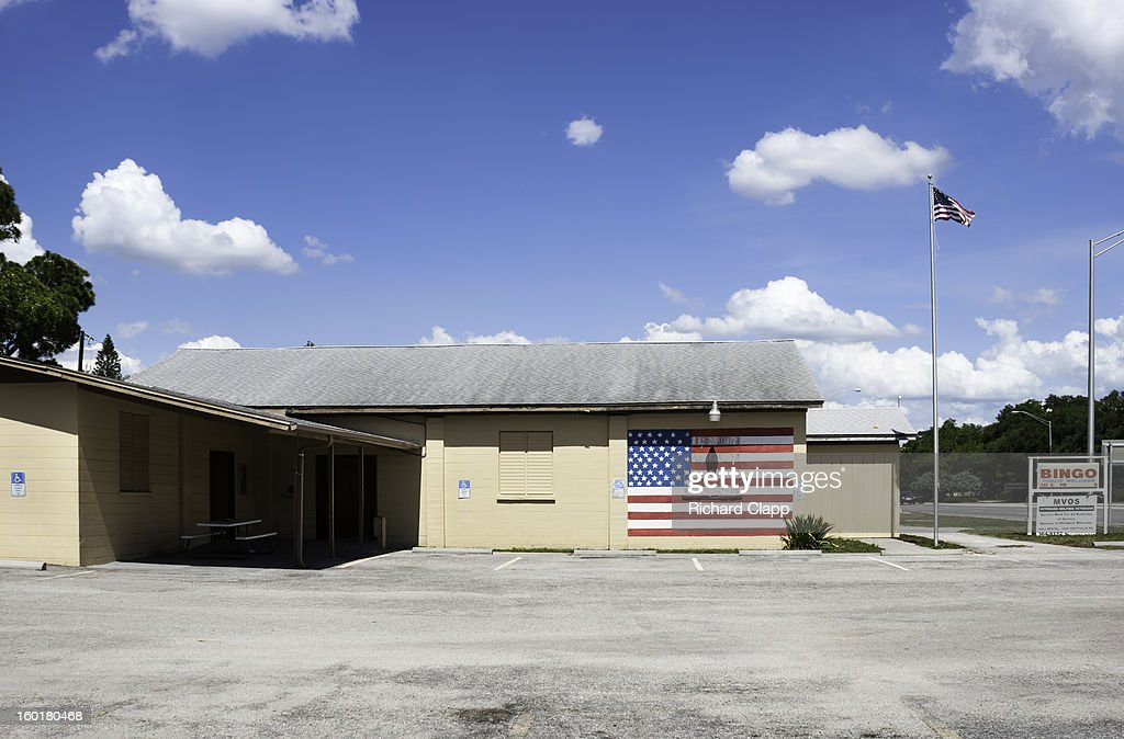 CONTENT] Bingo Hall operated by the Disabled Veterans (DAV Chapter 3). Building facade shows a large faded American flag. An American flag on a flag pole.