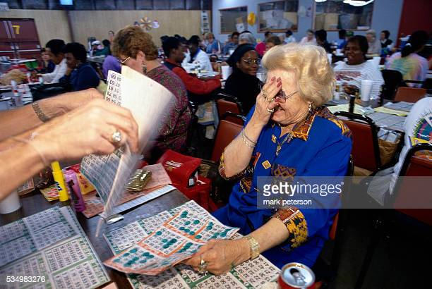 A bingo player puts her hand over her face as she gets new bingo cards The gambler is a member of Jeanne's Bingo Buddies a bingo club that travels...