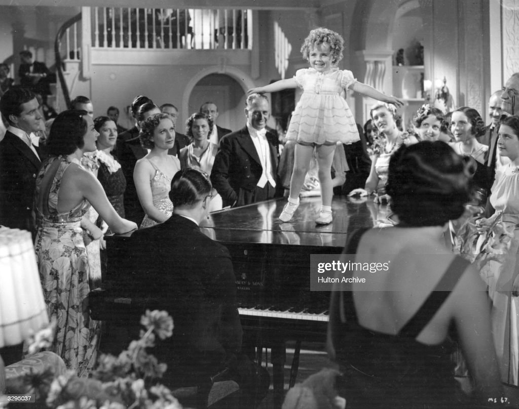Binkie Stuart (1932 - 2001), a <a gi-track='captionPersonalityLinkClicked' href=/galleries/search?phrase=Shirley+Temple&family=editorial&specificpeople=69996 ng-click='$event.stopPropagation()'>Shirley Temple</a> doppleganger, tap dances on a piano top to an admiring crowd in 'Little Miss Somebody'. The film was directed by Walter Tennyson for Mondover Studios.