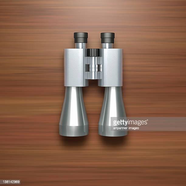 Binoculars on a wooden background