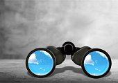 Close up of black binocular with sky in glasses isolated on white