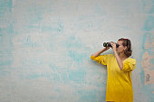 woman with binoculars on green background