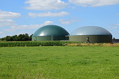 biogas plant for renewable energy on a green meadow against the blue sky with clouds