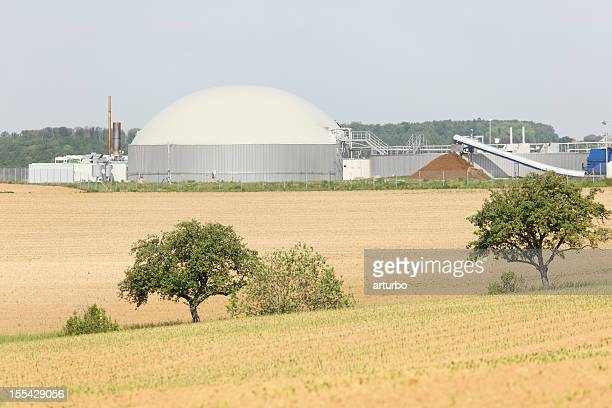 bio gas power generator  behind fresh planted field and trees