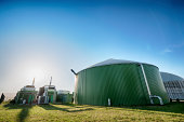 Wide angle shot of a modern biogas plant in summer. Back lit with some nice lens flare