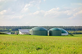 Biogas plant, barn with photovoltaics, tractor aside, green meadow in front