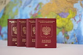 Biometric russian passports are in a row on the background of the world map. . The passport of the Russian Federation. The concept of tourism and travel.