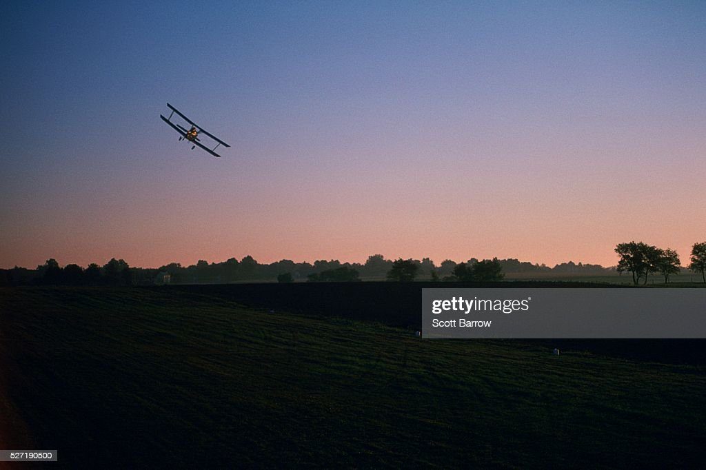 Biplane flying over a field : Stockfoto