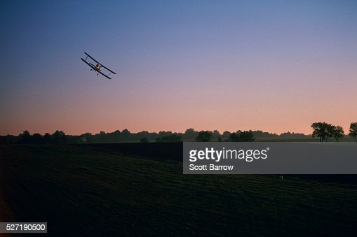 Biplane flying over a field : Stock Photo