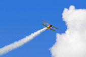 Biplane with a vapour trail, blue sky and cloud