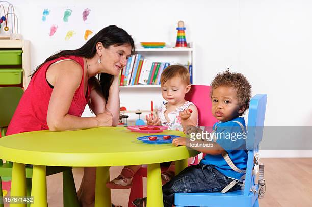 Biracial Baby Boy Looks Away While Carer Watches Peer