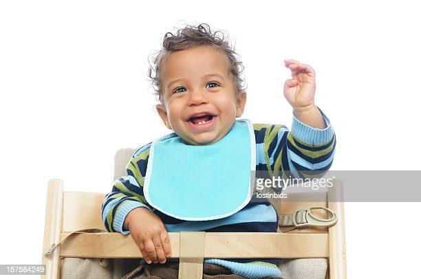 Biracial bebé mostrando su entusiasmo antes de una comida,