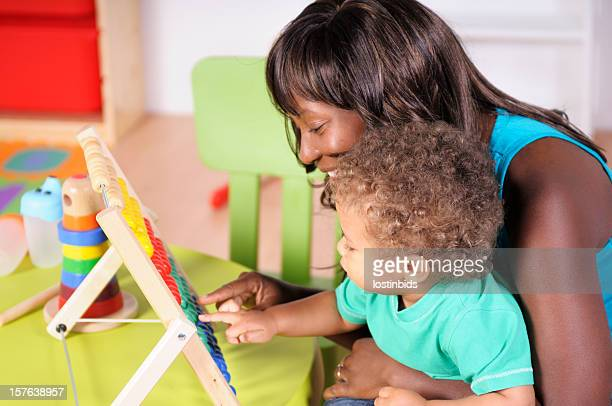Biracial Baby/ Toddler And African-American Woman Using Abacus