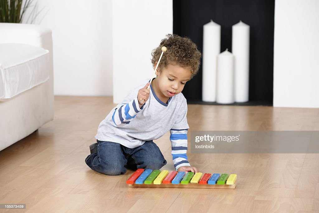 Biracial Toddler Playing With  Xylophone In The Living Room