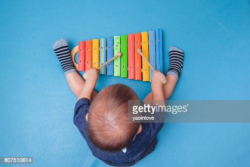 Bird eye view of Cute little Asian 18 months / 1 year old baby boy child hold sticks & plays a musical instrument colorful wooden toy xylophone : Stock Photo
