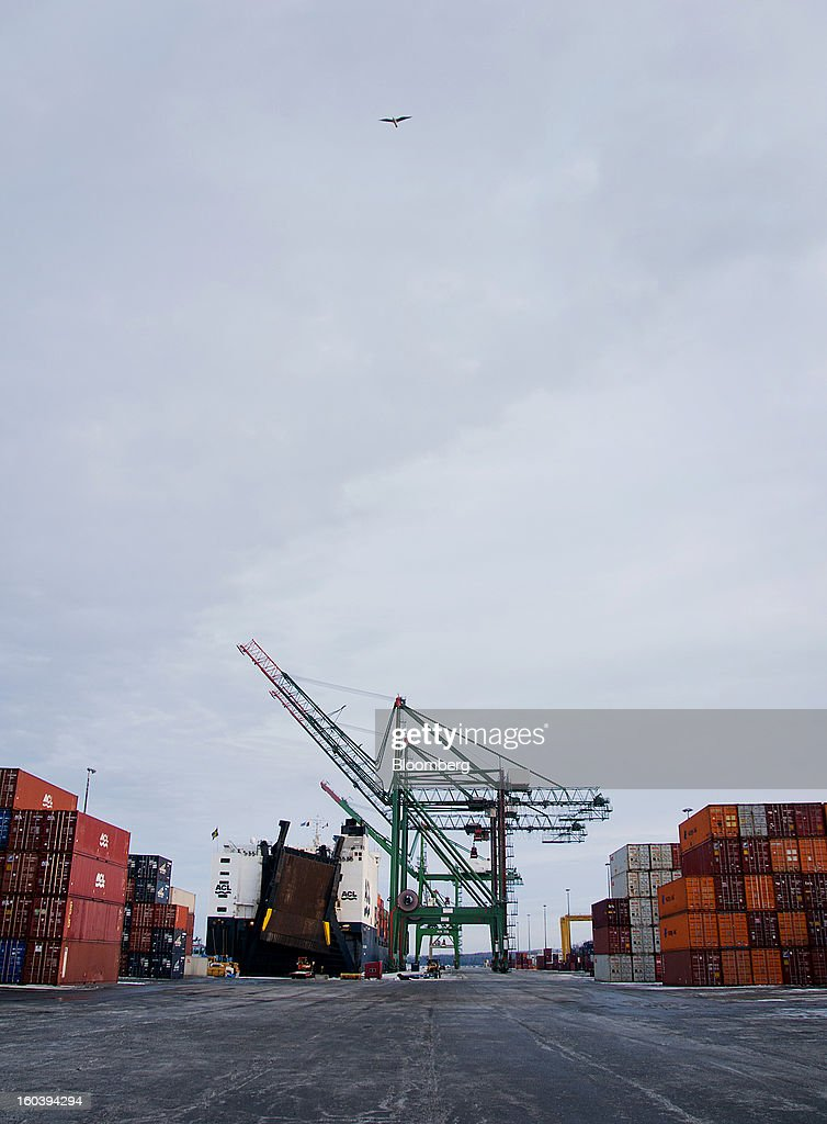 A bird flies over head as shipping containers are unloaded from an Atlantic Container Line (ACL) ship docked at the Port Of Halifax's Fairview Cove container terminal, operated by Cerescorp Co., in Halifax, Nova Scotia, Canada, on Wednesday, Jan. 30, 2013. Statistics Canada (STCA) is scheduled to release gross domestic product data on Jan. 31. Photographer: Aaron McKenzie Fraser/Bloomberg via Getty Images