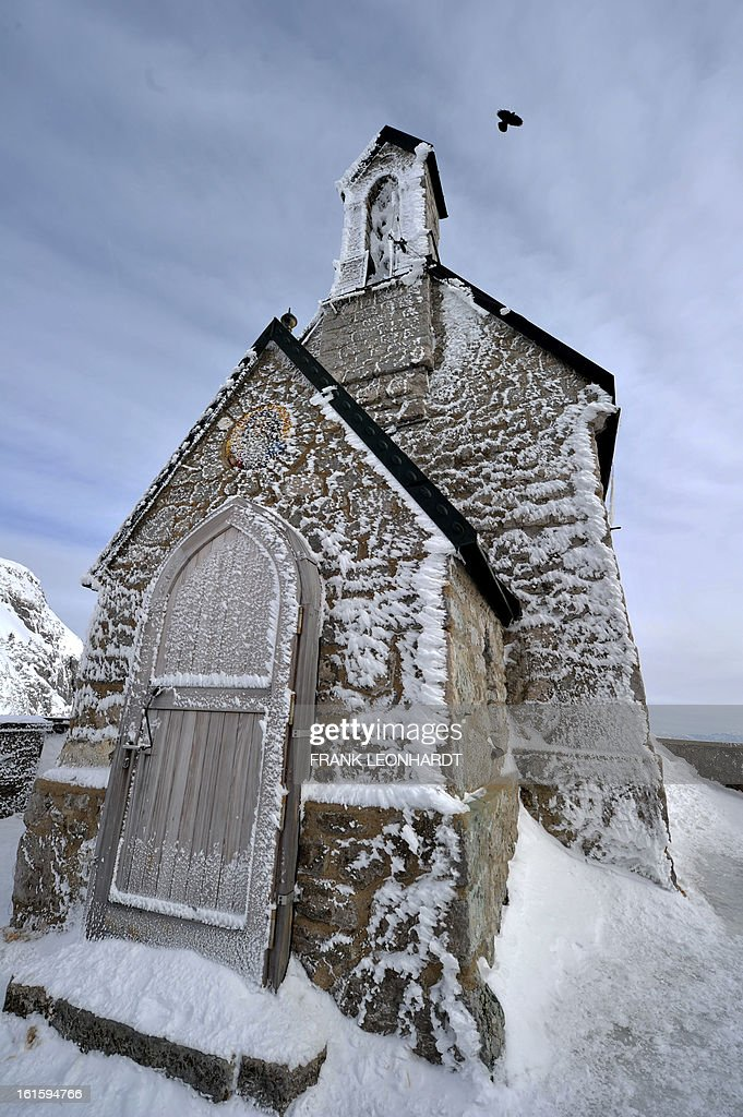 A bird flies over the ice covered Wendelstein-church on the Wendelstein, southern Germany, on February 12, 2013. AFP PHOTO / FRANK LEONHARDT GERMANY OUT